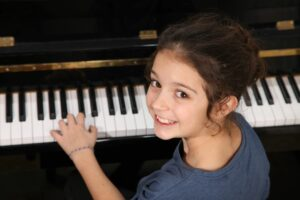 Young student at children's piano lessons looking over her shoulder